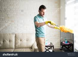 dusting furniture. Single Man Dusting His Furniture To Keep The Dust Away From Them And Have A Clean 2