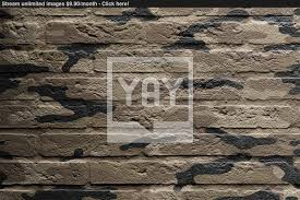 image of brick wall with a painting of a flag camouflage