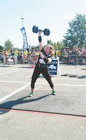 jackie bundus lifts a 90 pound dumbbell over her head as many times as she can at nationals