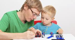Dad with five-year-old boy using tools to create toy car kit Great gifts for five year olds - BabyCentre UK