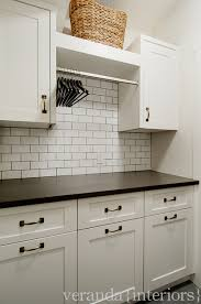 Great laundry area with storage galore! White cabinetry, subway tile  backsplash and drying rail.