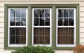 three new replacement windows with green trim on front of house horizontal