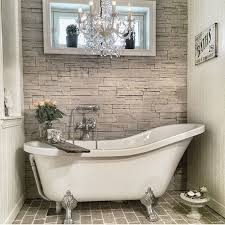 faux stone works as a perfect backdrop for a claw foot tub and a refined  chandelier