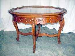 we have for an antique serving coffee table it is made of walnut with lots of detail carving the top lifts off with a serving tray the tray is glass