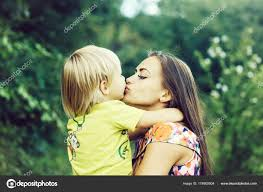 cute little child baby boy son kissing hugging pretty mother stock photo