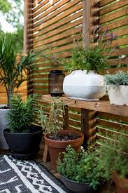 Patio slatted privacy screen with built-in shelf for potted plants