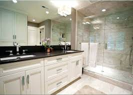 dark white bathroom cabinets under large mirror and also glass door shower area plus recessed lights