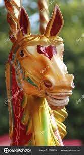 head of a wooden carousel horse on a fun fair ride photo by daseaford