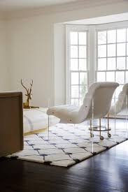 contemporary living room features a pair of white accent chairs with lucite base flanking a brass accent table on wheels atop a white and blue trellis rug
