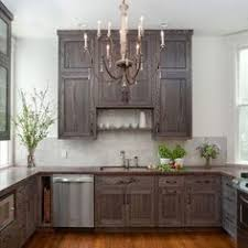 dark stained kitchen cabinets. Cottage Kitchen Features A French Candle Chandelier Illuminating Dark Stained Cabinets Paired With