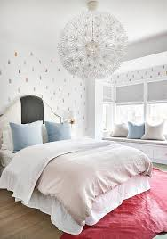 ali budd interiors lovely girl s bedroom features an ikea ps maskros pendant lamp hung over a red cowhide rug located beneath a bed dressed in gray and