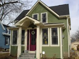 green siding cream trim black roof black windows red door red brick