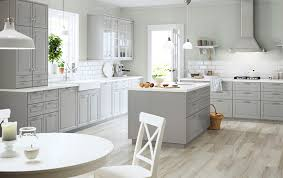 A large grey country kitchen with a lot of drawers, wall cabinets and a  kitchen