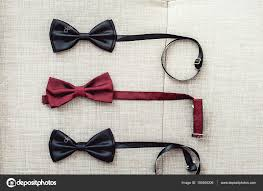 three bow ties two black and one red on a sofa team work career hipster wedding concept photo by