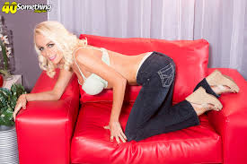 Brandi Anderson posing on a couch Photos Gallery