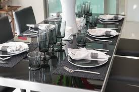 elegant glass top dining room table setup with six place settings for a dinner party with white cloth napkins and wine goblets
