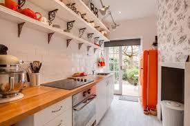 galley kitchen ideas with wood countertops and white brick backsplash plus orange fridge and orange smeg