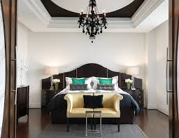 black crystal chandelier lighting. glamorous bedroom ideas with gold colored camel back sofa and black crystal chandelier lighting