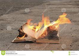 the old book burns on the asphalt with a bright flame