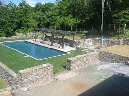 stone walls surround pool area with flagstone patios