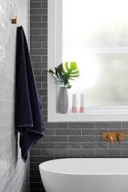 gray subway tiling behind white bathtub
