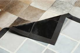 detail of a square tiles brown beige and black cowhide patchwork rug