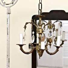 junk chandelier swings from chippy lamp stand