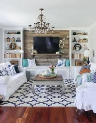 built in living room furniture. white sofas reclaimed wood accent wall builtin book cases blue and pillows rug a crystal lighting fixture built in living room furniture