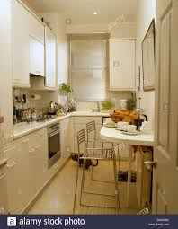 Modern white galley kitchen with chrome stools at breakfast bar set for  breakfast