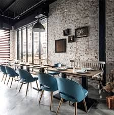 space with brick walls attractive paneling and furniture in retro style frames a greenery and wallpaper imitating books from a library make the
