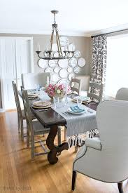 dining room in neutrals with ladderback side chairs upholstered wingback end chairs rope chandelier