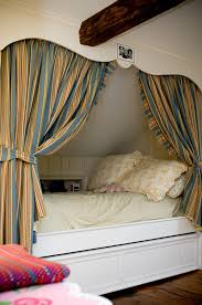 traditional kids bedroom with a cozy alcove bed featuring built in storage