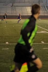 Referee Anthony Soblevesky runs by as Battle High School Olivia Sims runs  toward the goal   Photos   columbiamissourian.com