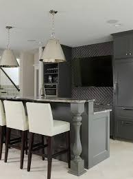 basement wet bar with dark gray cabinets and gray granite countertops