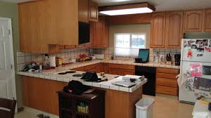Brown Cabinetry Using White Ceramic Tile For Countertop Also Backsplases In  Modern Small U Shaped Kitchen ...