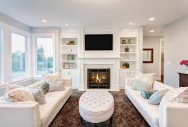 white built in shelves and cabinets with electric fireplace building in the center small settee