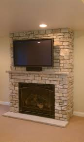 interior grey stone fireplace with grey mantel shelf and rectangle black metal firebox connected by