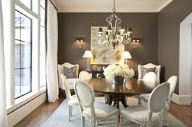 chic elegant dining room design with chocolate brown walls paint color walnut round dining tabe white leather louis chairs white wingback chairs