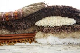 still life of wool tibetan blankets pillows and pelt rugs on wood table