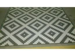 black and white patterned rug with teal green trim grey runner