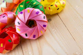 Coin Folding With Ribbon Is Shaped A Colorful Donut On Wood Texture