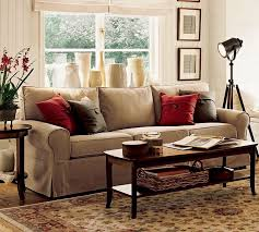 comfortable modern brown warm sofas living room with red cushions and wooden coffee table also tripod legs standing spot light