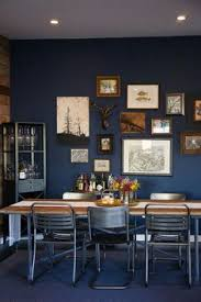dramatic blue dining room with a rustic wall gallery farmhouse table with mismatched chairs