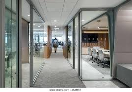 glass enclosed conference rooms along a corridor leading the open office desks park room crossword