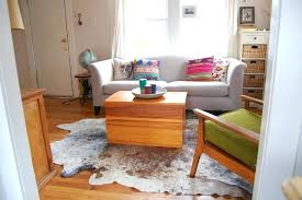 cowhide rug living room ideas wooden coffee table and soft grey couch with white cowhide rug