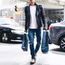 picture of blue ripped jeans a white tee a black leather jacket and ocher boots