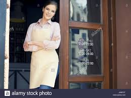 Waitress with arms crossed in front of cafe doors Stock Photo ...