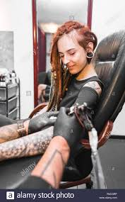 Girl With Dreadlocks In A Tattoo Parlor The Master Creates A