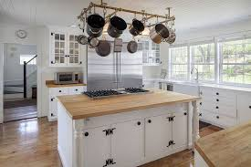 country kitchen with white glass panel cabinets maple wood countertops and island with built in