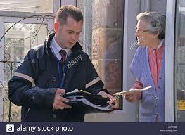door to door salesman talking to elderly woman Stock Photo ...